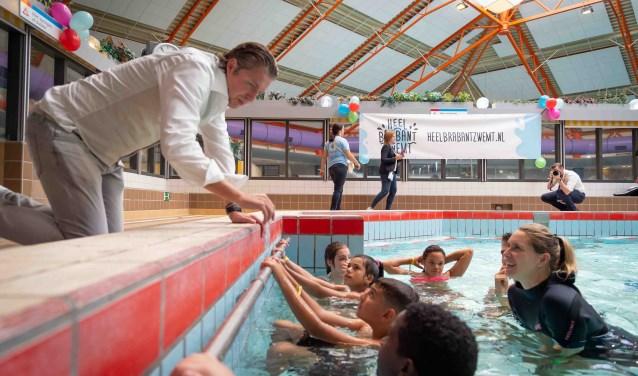 Onder toeziend oog van Brabantse Olympische zwemmers Pieter van den Hoogenband en Maud van der Meer leren kinderen zwemmen. FOTO: Heel Brabant Zwemt