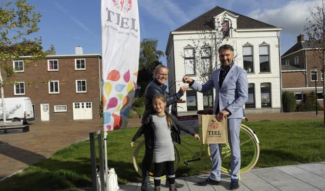 Mevr. Sonsseahray Van Dalen-de Keijzer neemt, samen met haar dochtertje Kaylee, de fietssleutels van de gewonnen Oma fiets in ontvangst, uit handen van Roland van Vugt, directeur Stadspromotie Tiel.