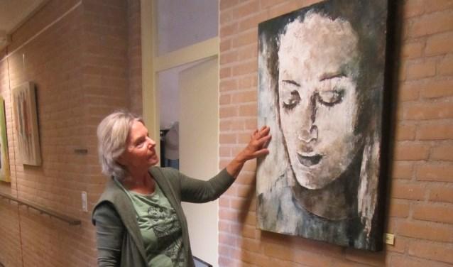 Miep Offenberg bij één van haar schilderijen