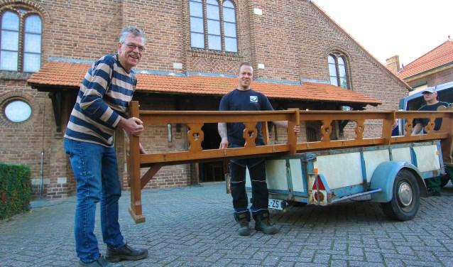 Ben Roelofs (links) plaatst met zoon Rob een kerkbank uit de kerk in Huissen-Zand op de aanhangwagen. (foto: Kirsten den Boef)