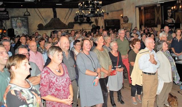 Een volle zaal laat zich aan het einde van de tiende Pecha Kucha Oirschot muzikaal op sleeptouw nemen door Michel Bergman.