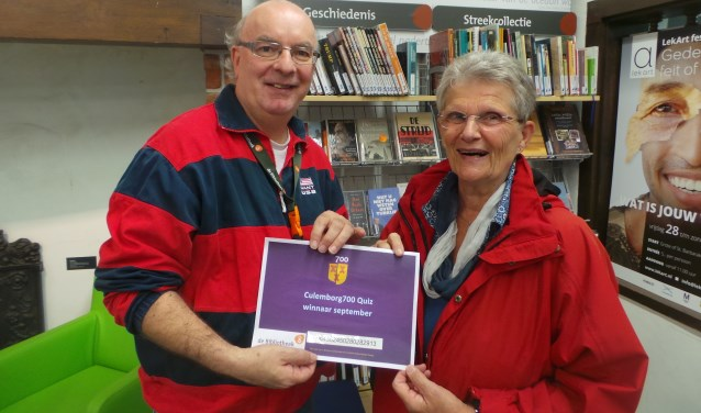 Herman Wevers (bibliotheek) overhandigt prijswinnaar Alies Derwig een boekenbon. (Foto: Bert Blommers)