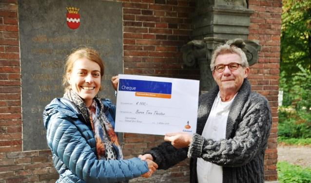 Judith de Gier overhandigt een cheque aan Peter de Rooij.