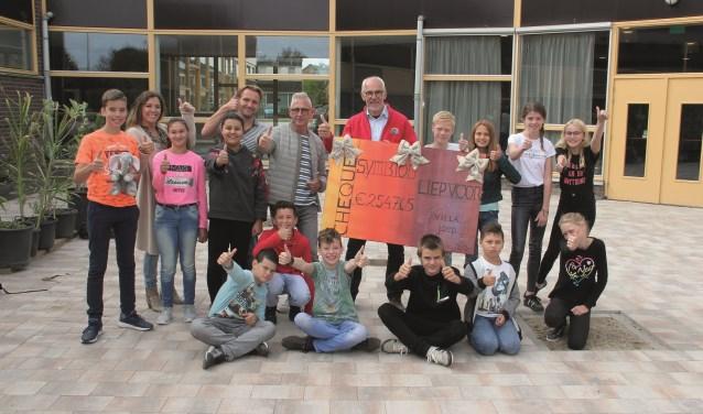 Leerlingen van Symbion overhandigden de cheque aan Hans Vos (met rode jas), ambassadeur van Villa Joep.
