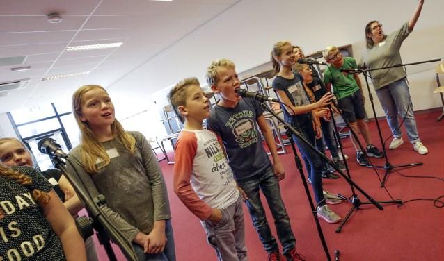 Leerlingen zijn bezig met het omgaan met de microfoon in de workshop Licht en geluid. Foto: Jurgen van Hoof.