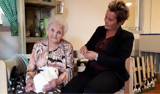 Mevrouw Quak-Geurkink (90) stroezelt met konijn Mies. Ze aait het konijn automatisch zodra het dier op schoot wordt gezet en praat tegen het dier. Beiden genieten van het contact. Anita van der Waal kijkt toe...