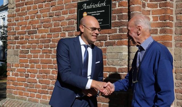 Wethouder Gerrit Boonzaaijer feliciteert een tevreden Huib van Alfen, koster van de Andrieskerk. FOTO: Hanny van Eerden