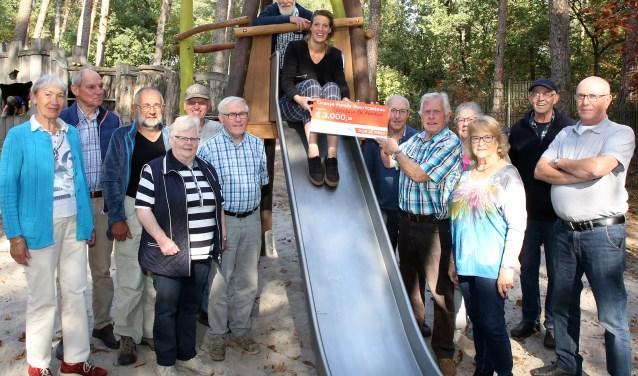 Op de foto een deel van de vrijwilligers met Marjolijn Breeuws van het Oranjefonss (op de glijbaan) die de cheque overhandigt aan voorzitter Huub Lanters van de KlimBim. Foto: Theo van Sambeek.