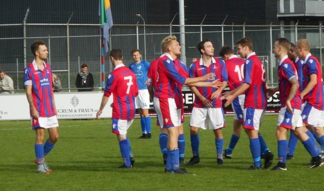 Maikel Steenbakker (derde van rechts) neemt de felicitaties in ontvangst nadat hij SC Emma op 5-2 heeft gezet.