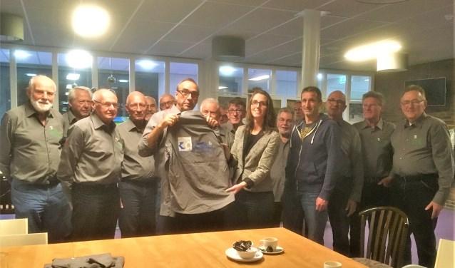 Jac Romeijnsen overhandigt het nieuwe overhemd aan Annika Dieleman. Rechts van haar Jeroen Brouwer van Totaltec