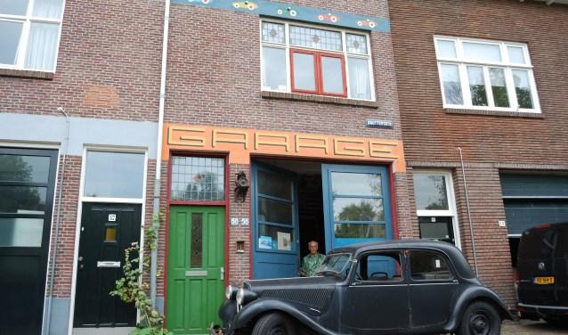 Rene Veenis, in de deuropening van zijn 'kasteel', schilderde vijf auto's op de gevel van zijn huis aan de Gruttersdijk. Foto: Sebas Bouquet