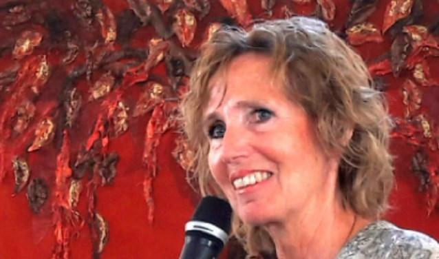 Jackie Howard bij een van haar werken, waarover ze enthousiast vertelt. Ze is er trots op te mogen exposeren in de Oude Kerk.