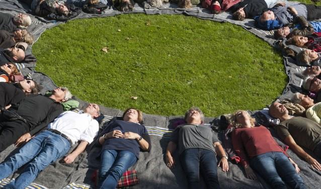 Een half uur stil liggen in Hemmen. Twintig tot dertig mensen doen mee aan het project van kunstenaar Rob Sweere. (foto: Ellen Koelewijn)