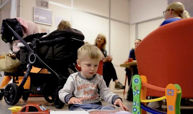 Terwijl moeders druk converseren houdt Aidan het liever bij een boek van Cars. (Foto: Max Timons)