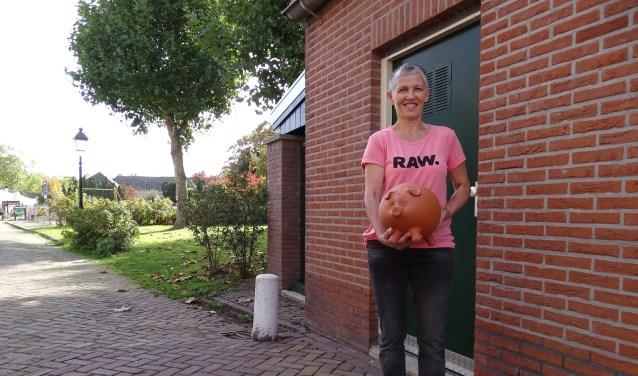 Maatje Metske laat bij haar garagedeur haar grote spaarpot zien. Hij moet vol voor Stichting Kinderen en Kansen. (Foto: Margreet Nagtegaal)