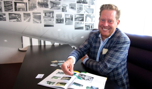 Jumbo-ondernemer zoekt in het historische boek over Elst bij welke tekst de fotoplaatjes in geplakt kunnen worden. (foto: Kirsten den Boef)