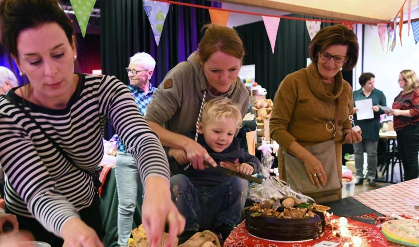 Stephanie Raes sneed haar winnende taart na afloop aan met assistentie van haar zoontje. Foto: Jan Wijten