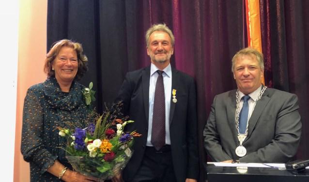 Van der Kooi (midden) ontving de onderscheiding uit handen van locoburgemeester Adrie Bragt.