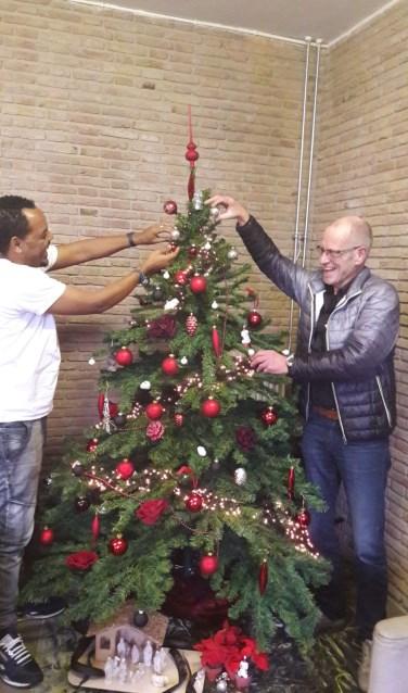 Vrijwilliger Henk Rijkers helpt een vluchteling met het optuigen van de kerstboom.