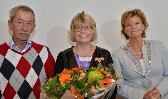 Een volledig verraste Mia van Jaarsveld-Kemp, geflankeerd door haar echtgenoot en burgemeester Petra van Hartskamp, ontving zondagmorgen een Koninklijk onderscheiding . (Foto: Paul van den Dungen)