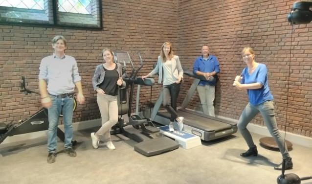 Artsen, therapeuten en apothekers poseren samen in de ker/fitnessruimte. Deze is onderdeel van het nieuwe gezondheidscentrum.