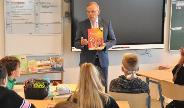 Burgemeester Jan Luteijn van de gemeente Cromstrijen leest voor over duurzamheid aan groep 8 van OBS De Boomgaard.