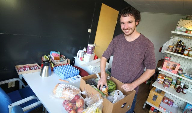 Bram van Eldik van Stichting GEEV pakt een voedselpakket in. (foto: Marco Diepeveen)