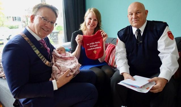 Burgemeester Patrick van Domburg en de heer Koos Dros van de brandweer op bezoek bij mevrouw Hofstee en baby Fenne. Mét brandveilige cadeautjes. (Foto: Bernard Brosi)