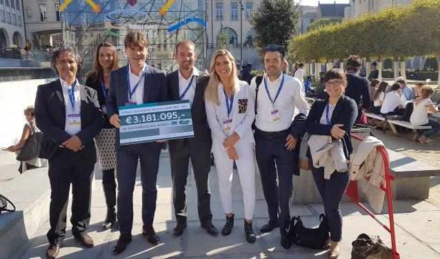 Trots toont de Bredase delegatie in Brussel hun 'cheque' met de subsidie van 80% op de begroting van 3,2 miljoen vanuit het Europese programma Urban Innovative Actions voor het project AirQon. FOTO: AIRQON