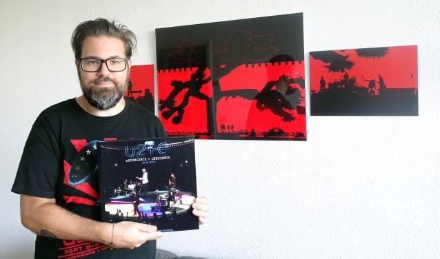 Danny met het boek, op de achtergond de foto's van U2 in de Arena 2017. (Foto: Privé)