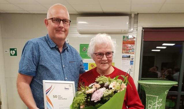 Andre van Veelen voorzitter van Nikantes overhandigt bloemen, oorkonde en een speld in verband met 50 jaar lid van het KNKV en Nikantes van Sijtje Groeneveld