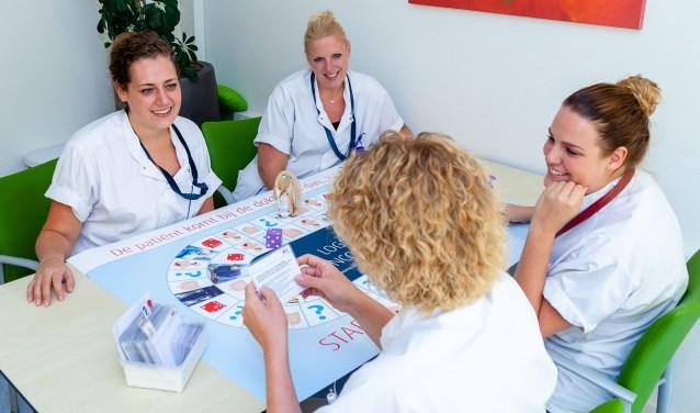 Annette Schellekens leest een vraag voor en speelt het spel met een aantal collega's. foto: J.Pistorius