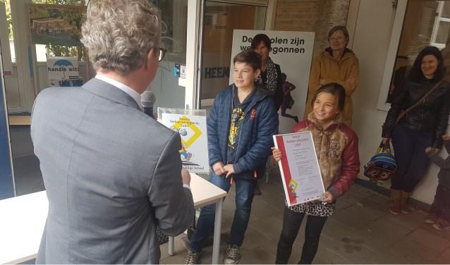 Aleksander en Senna, voorzitter en secretaris van de leerlingenraad, ontvingen gistermiddag het bordje uit handen van wethouder Gerard Gerrits. Eigen foto