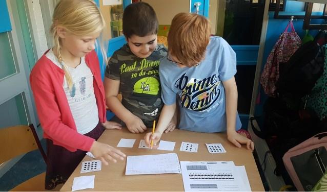 Met kaartjes leren de kinderen de computertaal van nullen en enen .