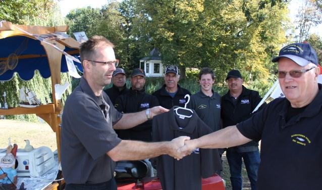Bertus ten Harkel (rechts) overhandigde de kleding aan de leden van de wedstrijdcommissie van H.S.V. De Slinge.