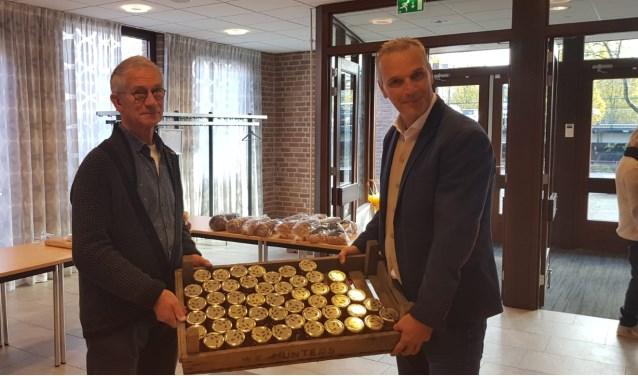 Wethouder Wim Vos overhandigt honing aan een vrijwilliger van voedselbank Leusden. (Foto: GL)