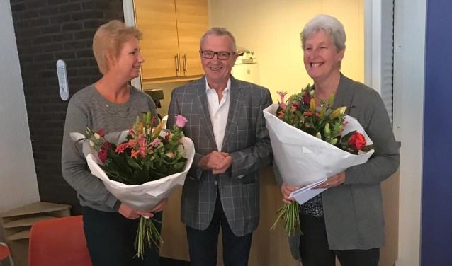 Evelien Schepers (links) en Gerrie Wennink worden in de bloemen gezet door regiovoorzitter Vincent Elferink.