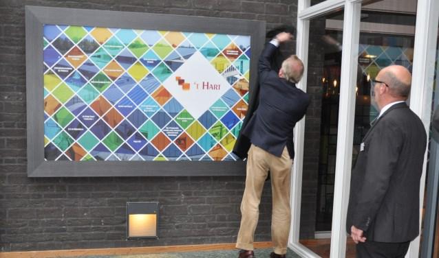 Wethouder Henk Plaizier onthult het kunstwerk met daarop de gebruikers van 't Hart. Jan van Bergen, een van de initiatiefnemers van de vernieuwing van de foyer, kijkt belangstellend toe.