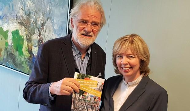 Voorzitter Rob Voorhuis overhandigt het BIZ-Meerjarenplan aan wethouder Ingrid Lambregts.