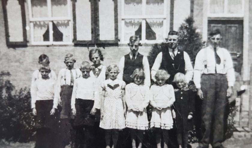 Familiefoto van Henricus (Driek) Verhoeven met zijn tien kinderen en zijn broer Gus. De foto is na het overlijden van zijn vrouw Antonia genomen.