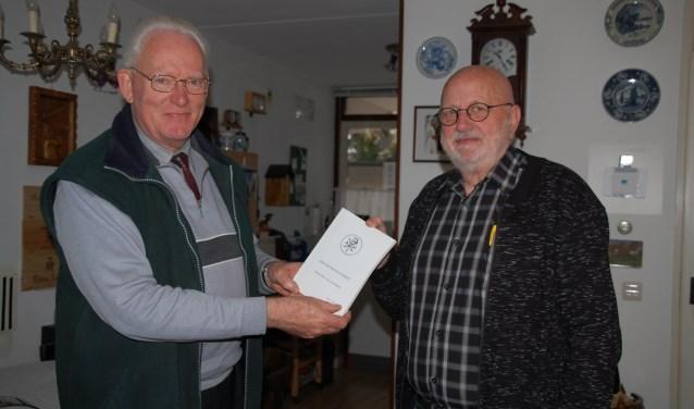 Drs. Beukhof (l) overhandigde de eerste uitgave van zijn boek aan meneer Wassink, voorzitter van de bewonersvereniging van de Dennenheuvel.