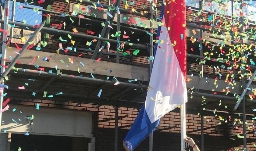 Rector Jeanette Warmels hijst de vlag bij het hoogste punt van de uitbreiding, die ook symbool staat voor flexibiliteit en transparantie van de school. (Foto: Cals College)