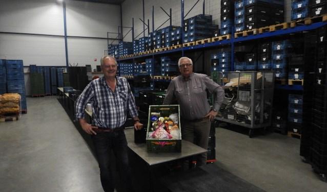Dirk van Kampen (links), voorzitter van de Voedselbank Alphen, en René de Jong, secretaris, in het pand in Ter Aar waar het niet-bederfelijke voedsel wordt bewaard. Op de tafel een voedselpakket.