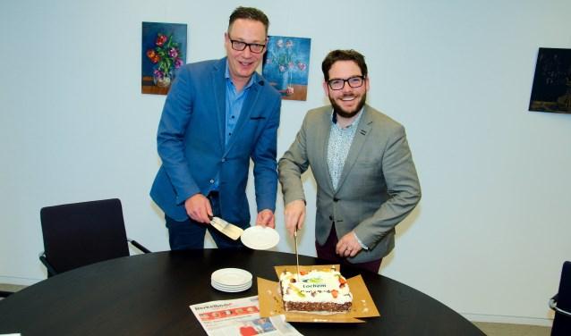 Peter Brongers van de Persgroep en burgemeester Sebastiaan van 't Erve snijden te taart aan om de vernieuwde samenwerking te vieren.