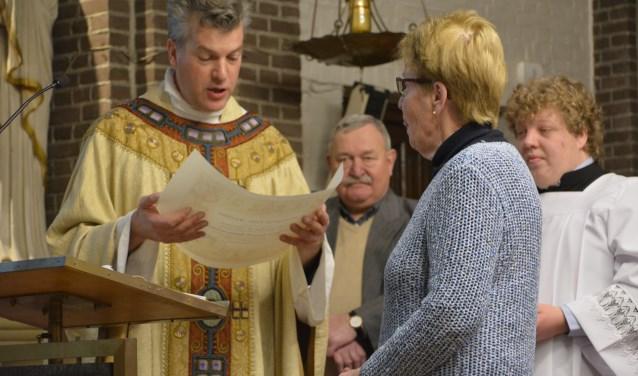 Pastoor Henri ten Have leest de pauselijke oorkonde voor aan Christien Maassen, in het midden Albert Schrasser
