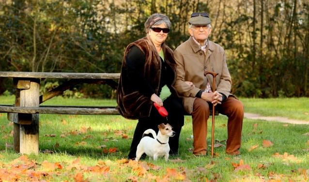 Twee senioren met een hondje.