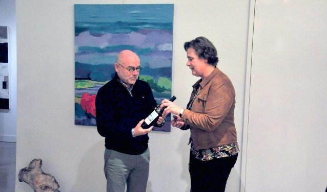 Henk Hulshof neemt de eerste fles met het nieuwe etiket in ontvangst van Neeltje Huisman, op de achtergrond het schilderij