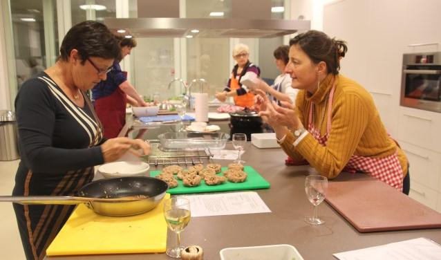 Sofia legt een recept uit aan één van de deelnemers tijdens een eerdere kook workshop
