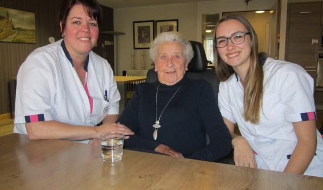 """Constance van den Akker, bewoonster Betsie van Orsouw (85) en Demi Heij in de gezamenlijke woonkamer van woonzorgcentrum De Wellen. """"Het is heel afwisselend. Geen dag is hetzelfde"""", vertelt Constance."""
