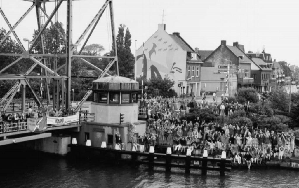 Studenten bij de brug, met een meer dan levensgrote geit op de zijgevel van het oude pand van installatiebedrijf J.J. van den Broek.  © Persgroep